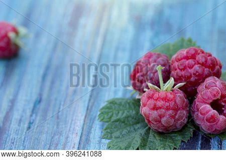 Raspberry Close-up. Right On A Blue Wooden Table Several Red Raspberries. Free Space For Text On The