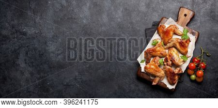 Hot barbecue chicken wings with sauce on cutting board. Flat lay. Top view on wide stone table with copy space