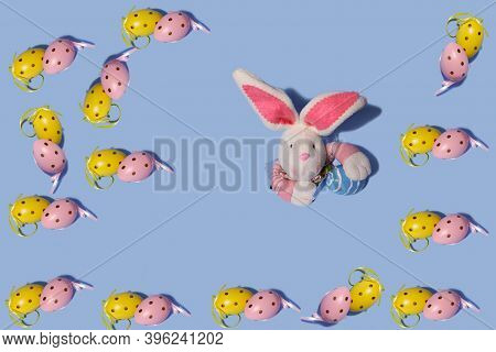 Easter Background. Easter Eggs Pattern. In The Center, A Rabbit Peeks Out Of Torn Paper. Horizontal,