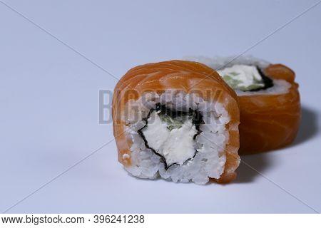 Food Background. Orange Rolls On   Light Background. Rolls Philadelphia Close-up. Rolls With Salmon