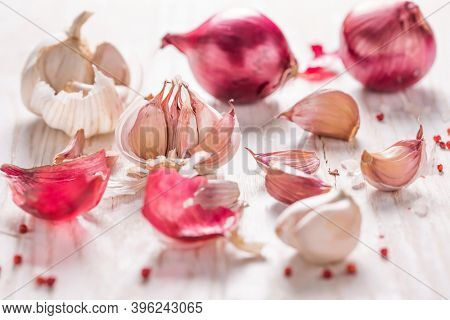 Garlic bulb, garlic cloves and red onions on white wooden background