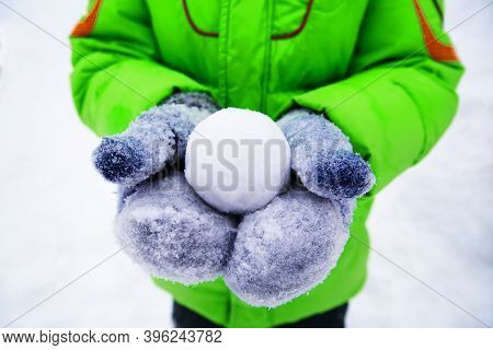 Snowball In Hands. Close-up Of Cropped Hands Holding Snowball
