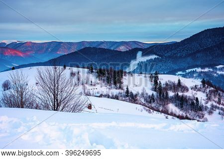 Winter Mountain Landscape At Sunrise. Trees And Fields On Snow Covered Hills. Ridge In The Distance