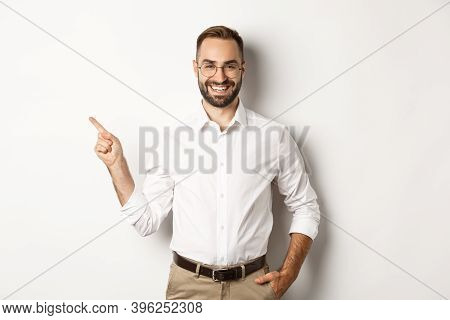 Confident Businessman Pointing Finger Left At Company Logo, Standing Over White Background