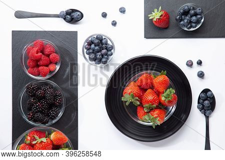 Composition With Berries In Glass Bowls, Slate Plates, And Spoons On White Background. Top View.