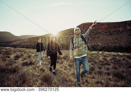 Group Of Active Teens Hiking Searching For Direction Pointing In The Distance Bonding In Luscious Se