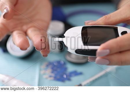 Woman Holding Glucometer Near Her Finger With Drop Of Blood Close-up. Blood Glucose Measurement In D