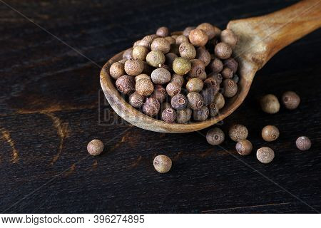Allspice In A Wooden Spoon On The Table