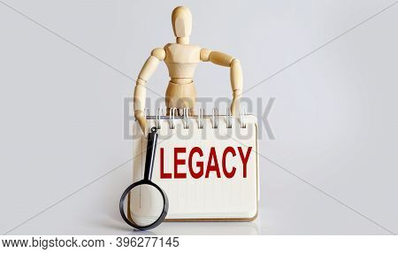 Wooden Man Shows With Hand To White Notepad With Text Legacy