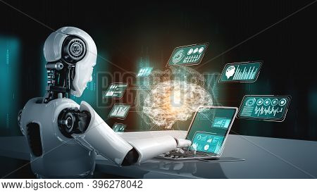 Robot Humanoid Use Laptop And Sit At Table For Big Data Analytic Using Ai Thinking Brain , Artificia