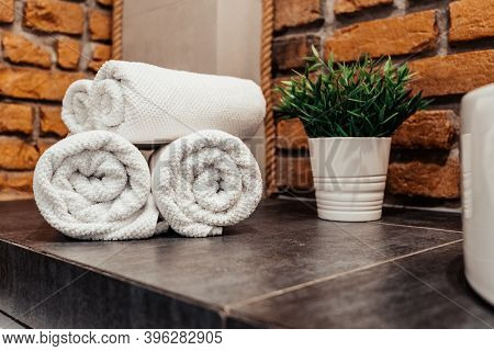 Corner Of The Bathroom On A Gray Surface White Towels Are Stacked In Rolls Loft Style Brick Walls Gr