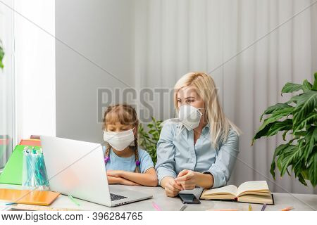 Young Woman In Medical Mask Pointing At Data On Laptop For Little Girl While Sitting At Table And Wo
