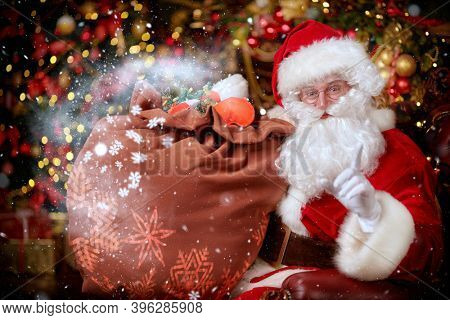 Magical Christmas time. Portrait of an emotional Santa Claus with a bag of gifts. Magic golden lights and snowflakes are around. Christmas and New Year concept.