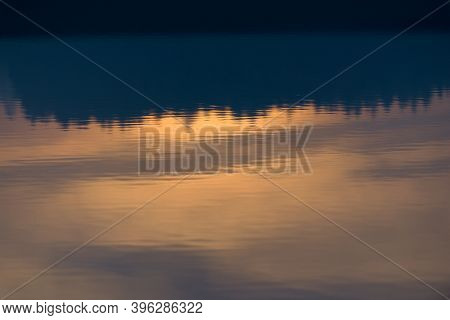 A Warm Orange Glowing Sunset Behind A Line Of Conifer Trees Is Reflected And Displayed Upside Down I
