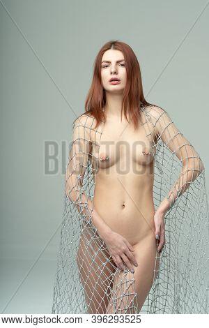 Young Beautiful Woman Posing Nude In The Studio, Holding A Fabric Mesh
