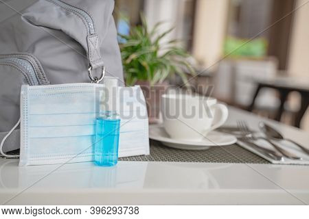 Bottle Of Alcohol Spray And Blurred Surgical Mask , Lady Bag On White Table In Open Air Restaurant ,