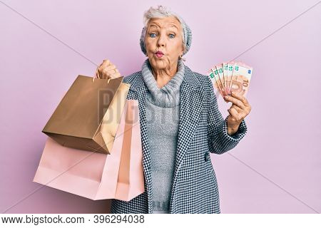 Senior grey-haired woman holding shopping bags and euros banknotes puffing cheeks with funny face. mouth inflated with air, catching air.