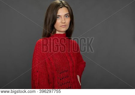 Tired Pretty Long-haired Brunette Girl Posing In Red Sweater Looking At Camera On Gray Studio Backdr