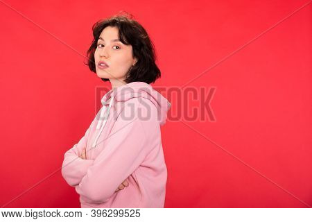 Pretty Brunette Girl In Pink Hoodie Posing Looking At Camera On Red Studio Backdrop Copy Space. Wome