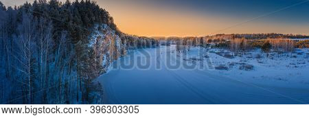Winter landscape. Sunset over mountain cliff and snowy river panorama.