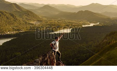 Hiker With A Backpack At Sunset On The Top Of A Mountain Enjoying The Sunset With A Raised Hand In A