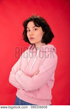 Pretty Brunette Girl In Pink Hoodie Posing Looking At Camera On Red Studio Backdrop. Womens Freedom,