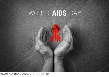 Red Ribbon In Hands On Gray Background, World Cancer Day, Symbol Of Fight Against Hiv, Aids And Canc