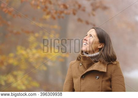 Happy Middle Age Woman Contemplating Views Looking At Side In A Forest In Fall Season
