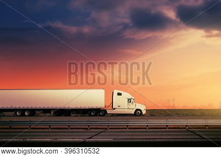 White freight truck driving on freeway road under red sunset sky.