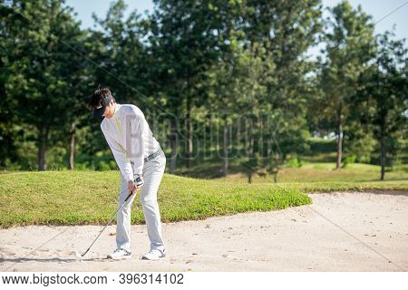 Asia Golfer Man Hitting Out Of A Sand Trap. The Golf Course Is On The Sand.  Hobby In Holiday And Va