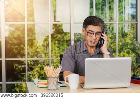 Asian Executive Senior Businessman Sitting On Desk Office He Using His Mobile Phone And Talking With