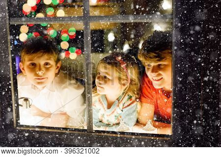 Three Cute Children Sitting By Window On Christmas Eve. Two School Kid Boys And Toddler Girl, Siblin