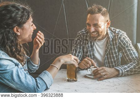 Engaged Couple Laughs And Jokes In A Bar - Friends Have Fun While Having A Drink In A Coffee Bar - W