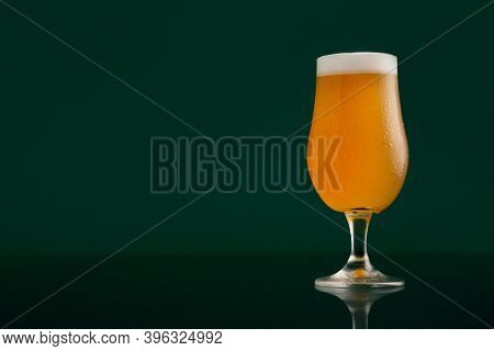 Light Craft Lager And Favorite Drink In Pub In Evening. Cold Glass Of Light Beer With Foam And Flowi