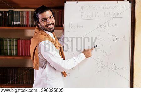 Remote Modern Education. Indian Teacher Man Teaching Online Pointing To Blackboard Explaining Englis