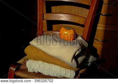 Stack Of Warm Knitted Sweaters In Sunlight On Wooden Chairs Across Wooden Dresser Close-up And Orang