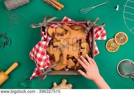 Top View Of Childs Hand Reaching Freshly Backed Christmas Gingerbread Cookie Deer Form Over Green Ba