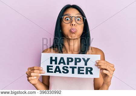 Young african american woman holding happy easter message paper puffing cheeks with funny face. mouth inflated with air, catching air.