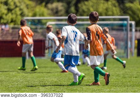 Boys Playing In A Soccer Match. Football Youth Players Kicking Football Ball In Sunny Day. Football