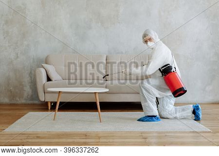 Male Disinfector In A Protective Suit And Mask Sprays Disinfectants In The House Table And Sofa Prev
