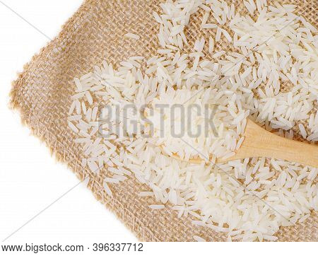 Isolated Rice On Wooden Spoon. Raw And Uncooked Rice In Wooden Spoon On Hemp Sackcloth Over White Ba