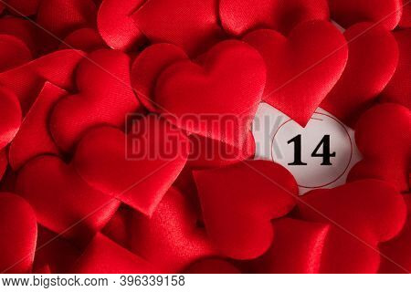 Valentine's day red silk hearts on calendar with 14 february date background, love, celebration concept