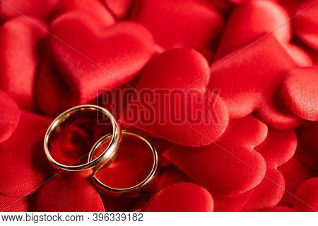 Two golden wedding rings on red hearts background