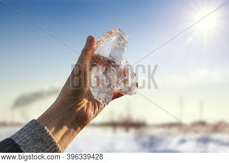 Ice In A Man's Hand Against The Backdrop Of The Bright Sun. Global Warming Concept. Seasonal Weather