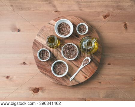Flax Seeds And Flaxseed Oil On Wooden Table. Set Of Small Bowls With Organic Flax Seed Or Linen Seed