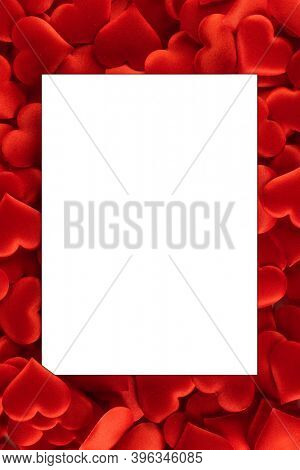 Valentine's day many red silk hearts background , border frame with white card with copy space, love concept