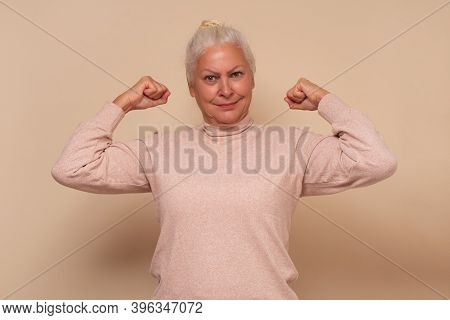 Confident Elderly Happy Senior Woman Showing Her Muscles Being Strong.