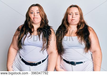 Plus size caucasian sisters woman wearing casual white clothes puffing cheeks with funny face. mouth inflated with air, crazy expression.