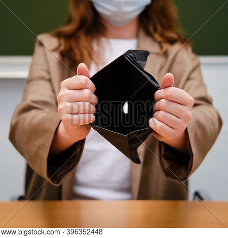 Teacher In Face Mask Holding Empty Wallet With No Money. Learning Difficulties In The Flu Pandemic.