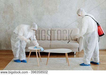 People In A Protective Suit With A Disinfectant Sprayer To Disinfect Household And Furniture. The Co